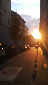 Blurry view on a Brussels street lit by a setting sun.
